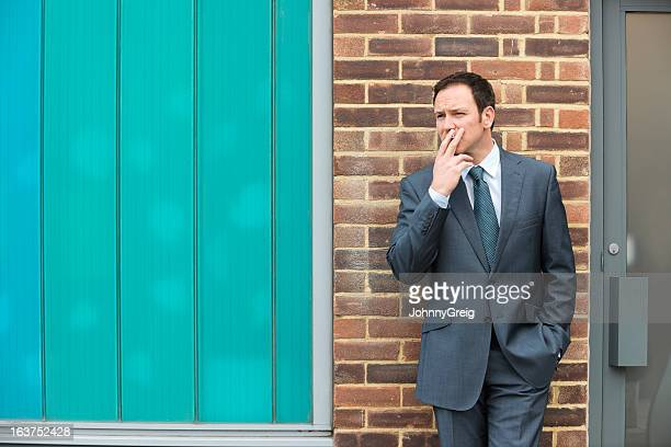 Businessman Smoking Cigarette Outdoors