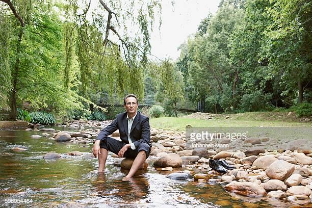 Businessman Soaking Feet in Stream