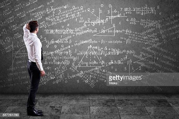 businessman solving mathematical equation - problems stock pictures, royalty-free photos & images
