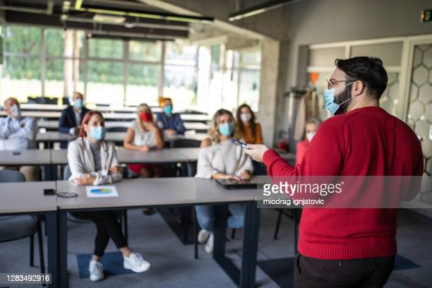 businessman speaking in front of audience during education training class - attending stock pictures, royalty-free photos & images