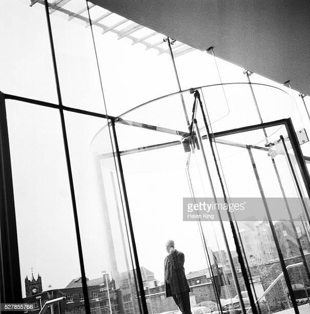 Businessman Speaking on Cell Phone Outside Lobby Door