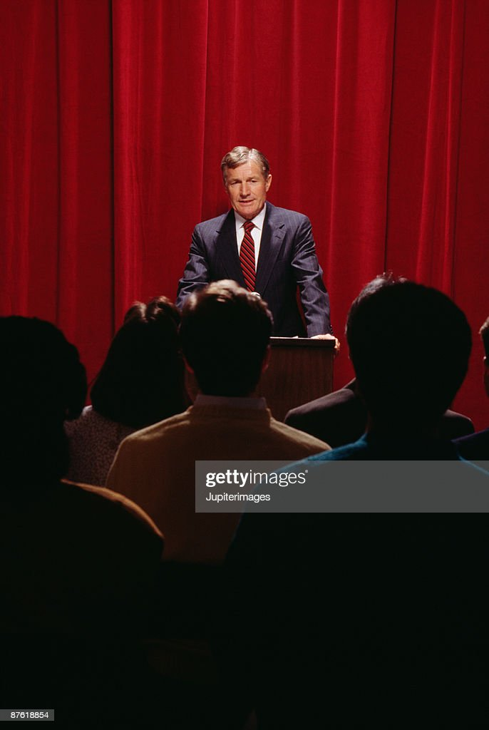 Businessman speaking to audience from stage : Stock Photo