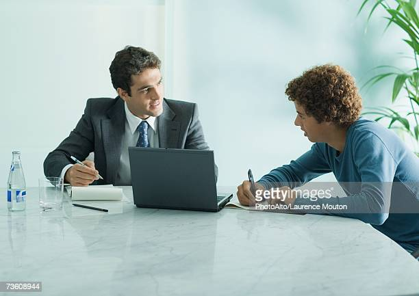 Businessman speaking to casually dressed young adult male, sitting at table