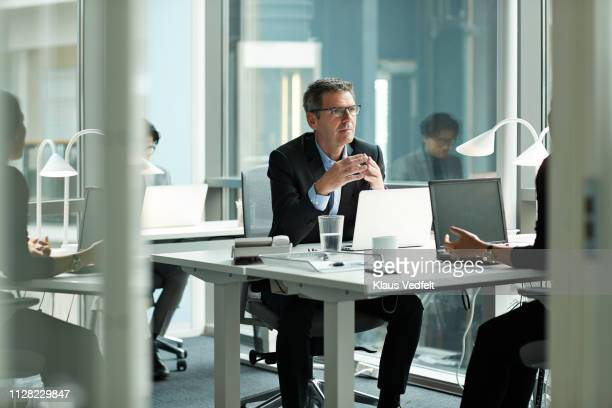 businessman speaking with co-worker in open office - incidental people stock pictures, royalty-free photos & images