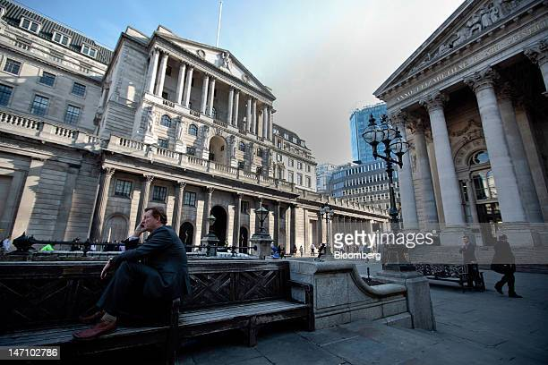 A businessman speaks on a mobile phone while sitting on a street bench outside the Royal Exchange right and Bank of England left in London UK on...