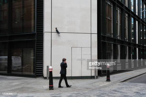 Businessman speaks on an mobile phone as he walks in the financial district of the City of London, U.K., on Monday, Sept. 7, 2020. U.K. Workers are...