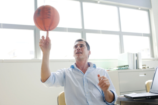 Businessman spinning a basketball on finger in office - gettyimageskorea