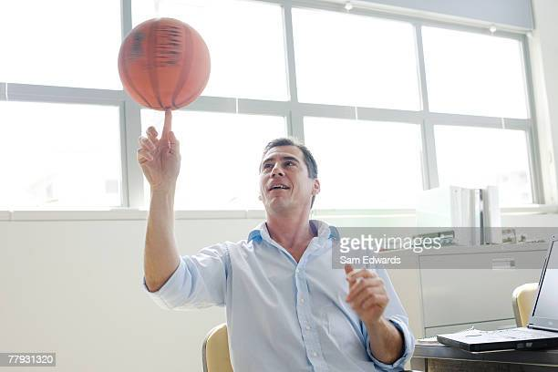 businessman spinning a basketball on finger in office - spinning stockfoto's en -beelden