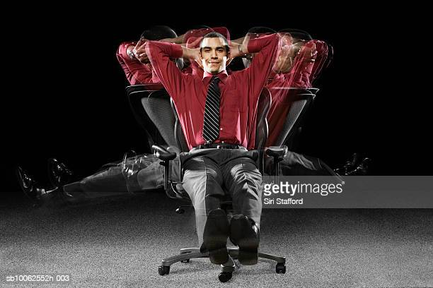 Businessman spinning on chair with hands behind head, smiling