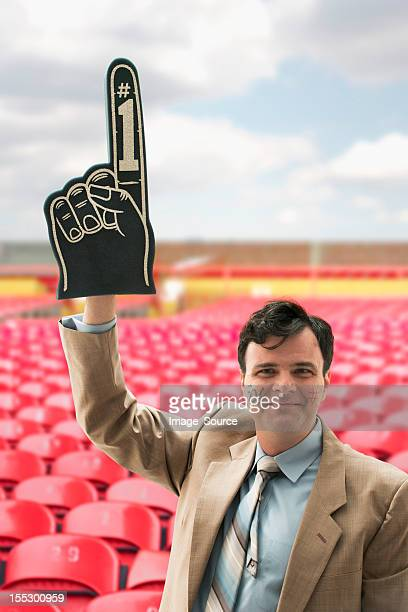 businessman sports fan with foam hand - foam finger stock photos and pictures