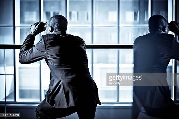 Uomo d'affari con il binocolo spionaggio