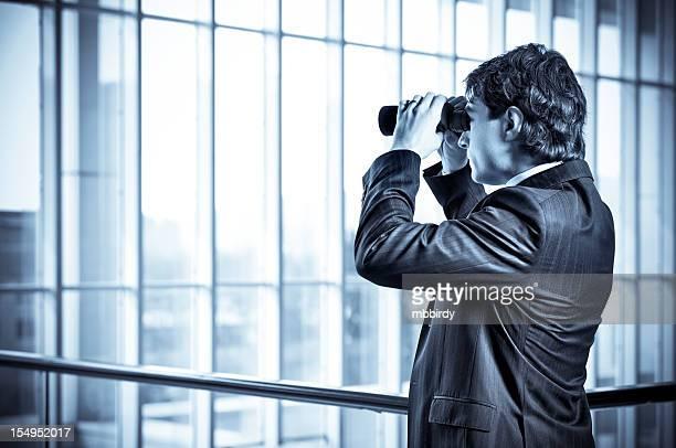 Businessman spying with binoculars