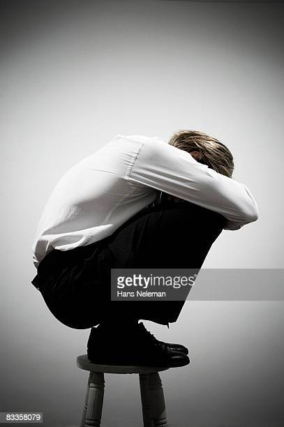 Businessman squatting on a stool
