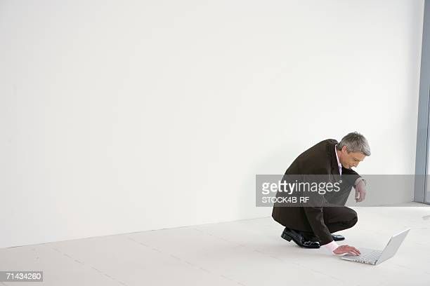 Businessman squatting on the floor working on laptop