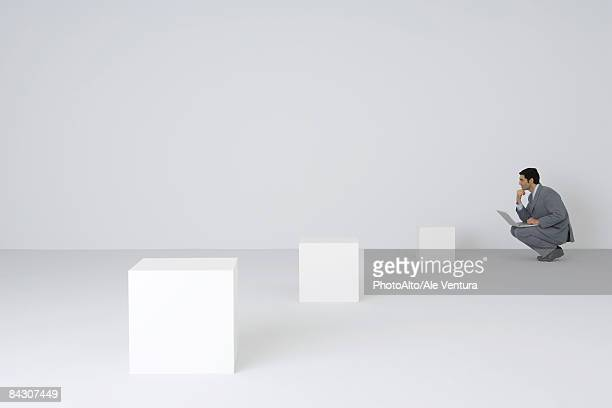Businessman squatting using laptop, looking at empty pedestals