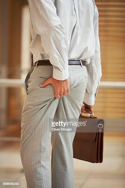 businessman squeezing his behind - oliver eltinger stock-fotos und bilder