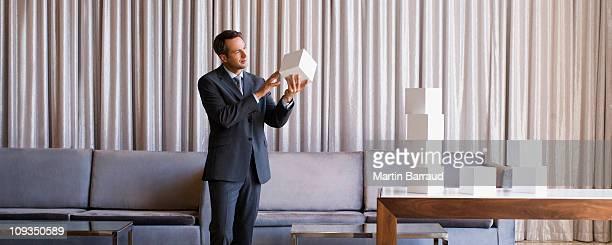 Geschäftsmann Stapeln weißer Würfel in der hotel lobby