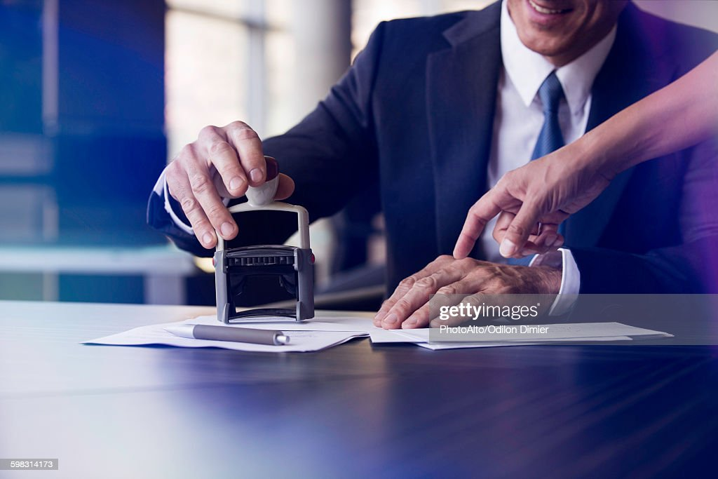 Businessman stamping document with help of assistant : Stock Photo
