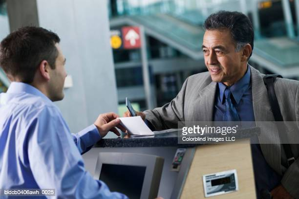 Businessman standing across a young man at an airport counter