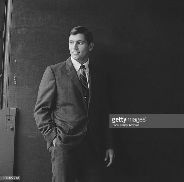 Businessman standing against black background, smiling