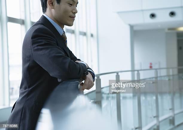 Businessman standing against railing