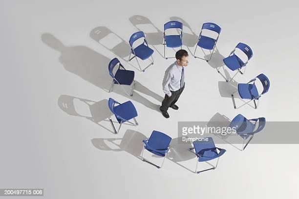 businessman standing alone in circle of chairs, elevated view - cadeira dobrável - fotografias e filmes do acervo