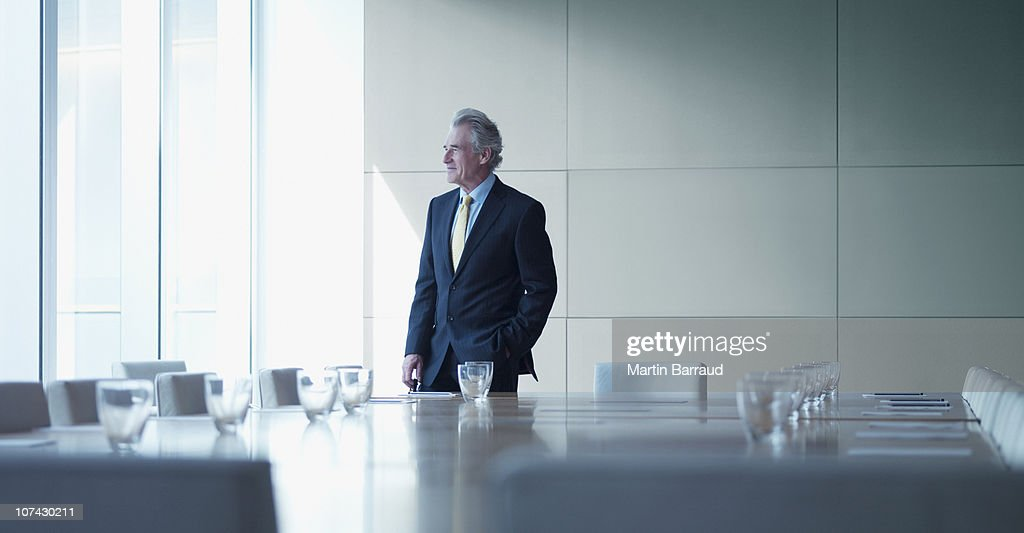 Businessman standing alone in conference room : Stock Photo