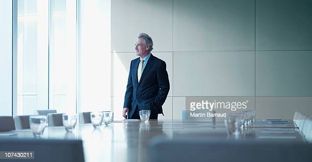 businessman standing alone in conference room - formal businesswear stock pictures, royalty-free photos & images