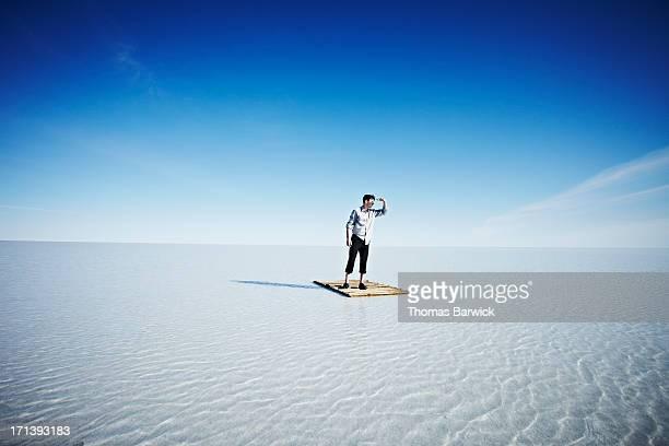 Businessman standing alone on life raft