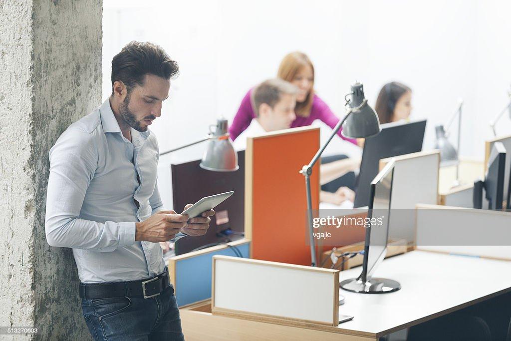 Homme daffaires debout et à laide de tablette numérique de bureau