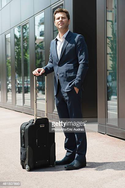 Businessman standing and waiting with luggage