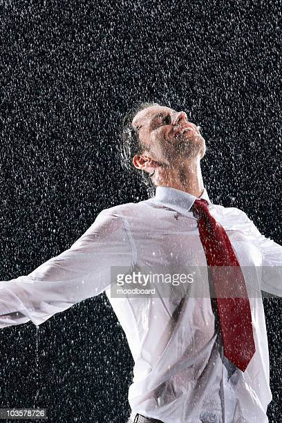 Businessman standing, arms spread facing incoming rain