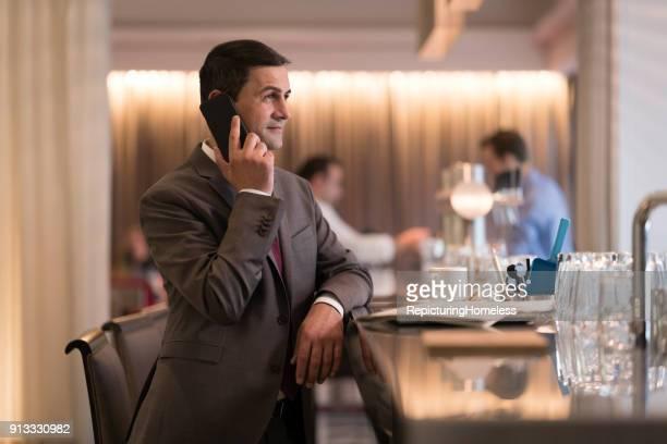 Ein Geschäftsmann steht an einer Bar in einem Hotel und telefoniert