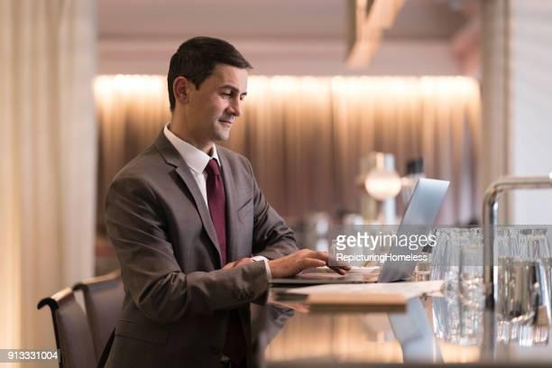 Ein Geschäftsmann steht an einer Bar in einem Hotel und arbeitet an seinem Laptop