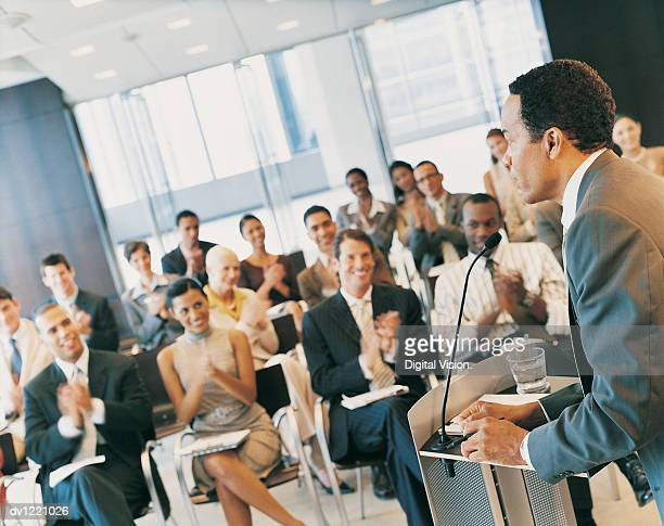businessman standing at a podium and giving a speech to a conference room full of delegates - conferenza di lavoro foto e immagini stock