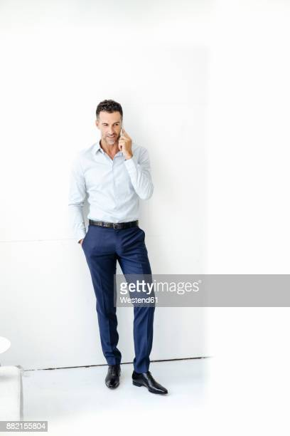 businessman standing at a wall talking on cell phone - businesswear stock pictures, royalty-free photos & images