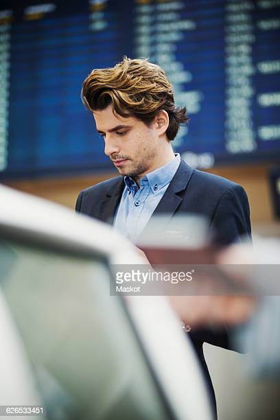 businessman standing at airport check-in counter - differential focus stock pictures, royalty-free photos & images