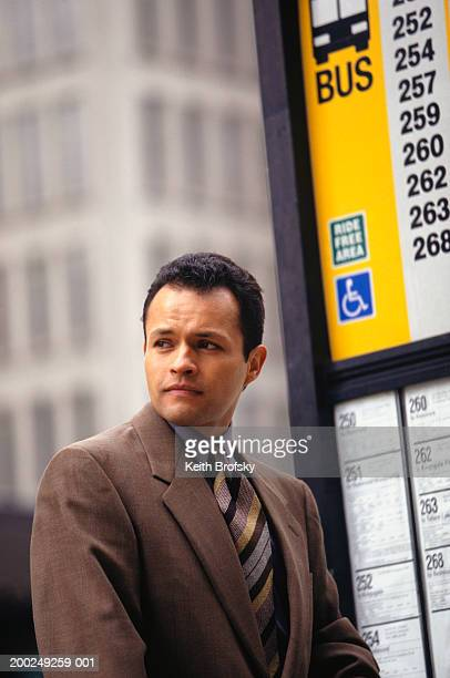 Businessman standing at bus stop in city centre