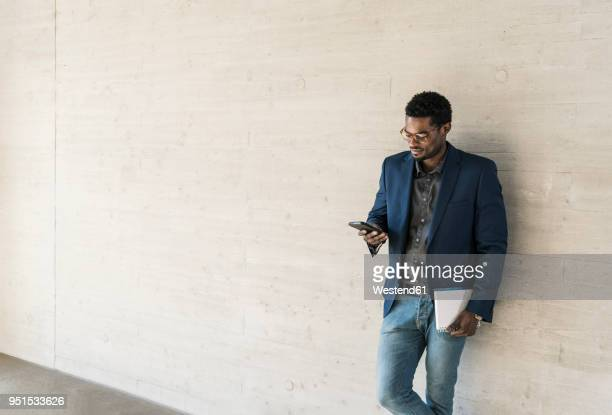 Businessman standing at concrete wall looking at cell phone