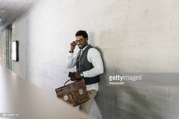 businessman standing at concrete wall with earphones, cell phone and briefcase - inserting stock pictures, royalty-free photos & images