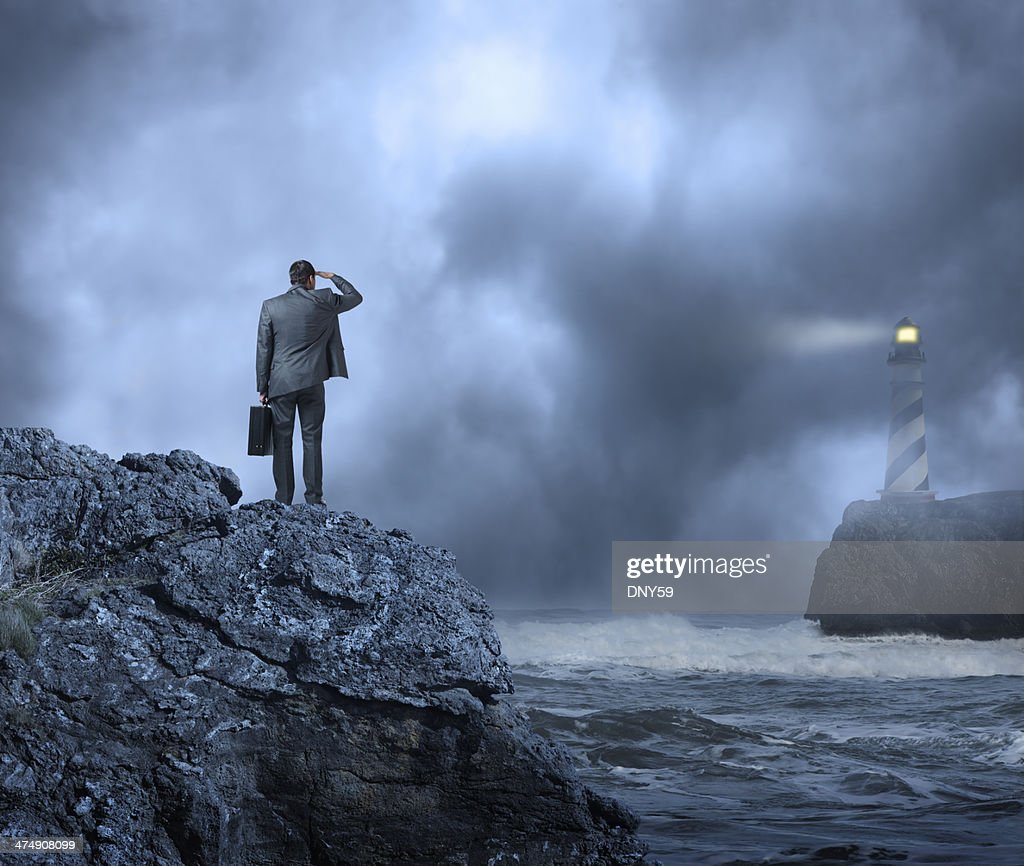 Businessman standing at edge of water looking towards a lighthouse : Stock Photo
