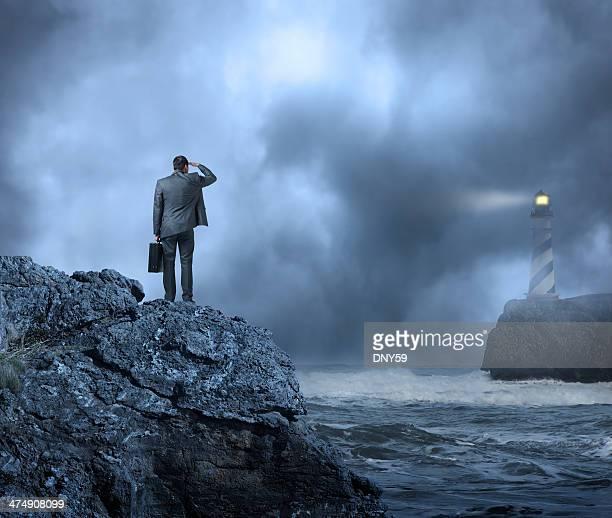Hombre de negocios de pie en la orilla del agua mirando hacia un faro