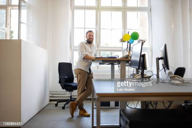 businessman standing at ergonomic desk in office - 人間工学 ストックフォトと画像