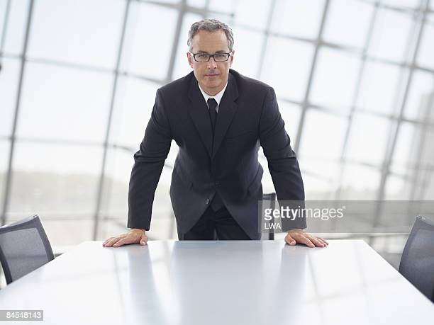 businessman standing at head of conference table - bending stock pictures, royalty-free photos & images