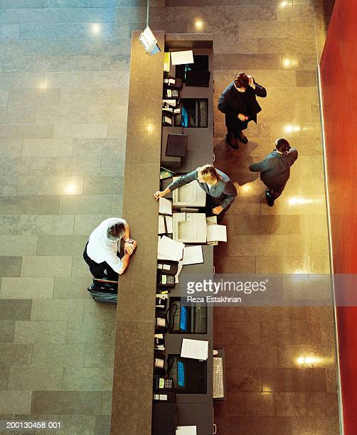 Businessman standing at hotel reception desk, overhead view