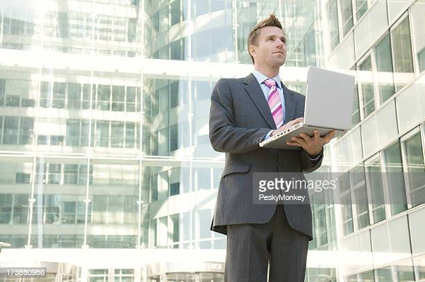 Geschäftsmann, stehen in modernen Büro arbeiten am Laptop