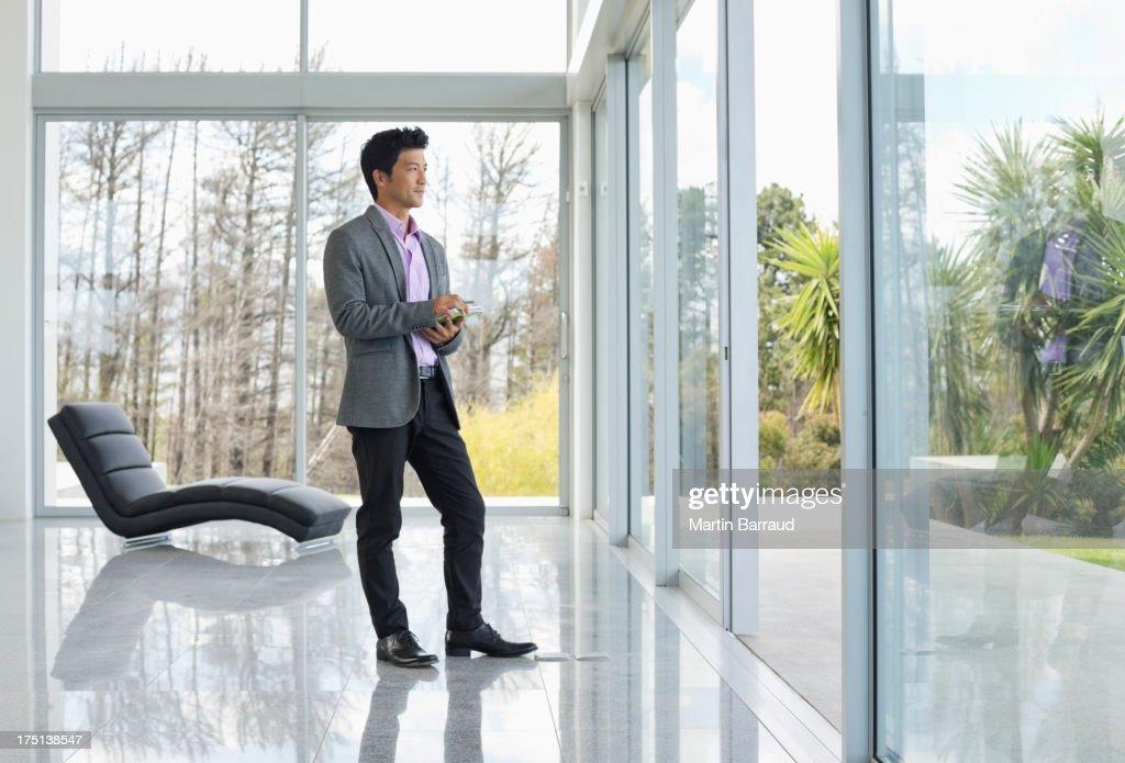 Businessman standing at office window : Stockfoto