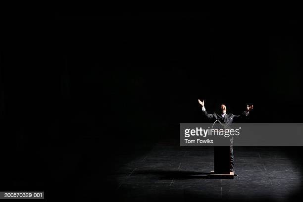 Businessman standing at podium, arms raised, illuminated by spotlight