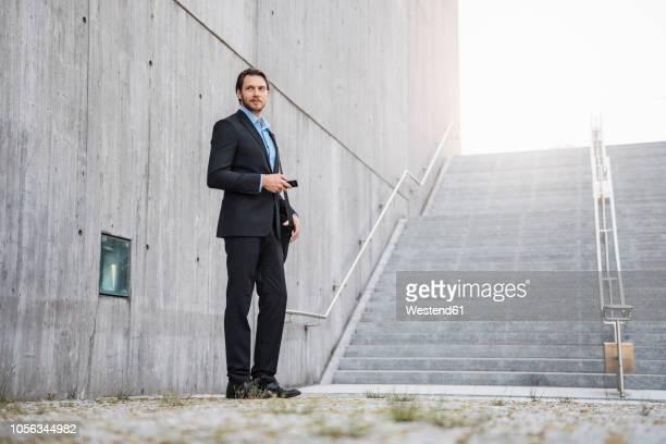businessman standing at stairs holding smartphone - ローアングル ストックフォトと画像