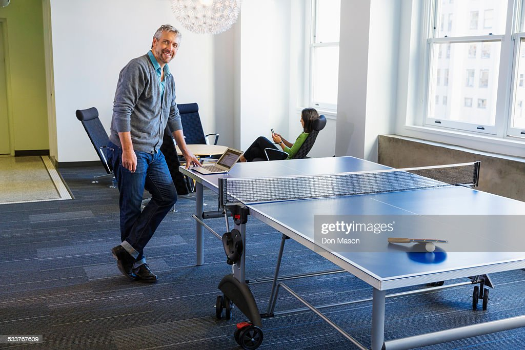Businessman standing at table tennis table in office : Foto stock